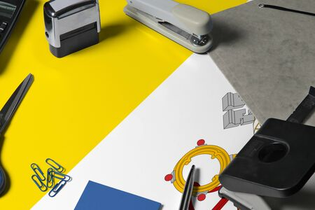Vatican City flag with office clerk workplace background. National stationary concept with office tools.