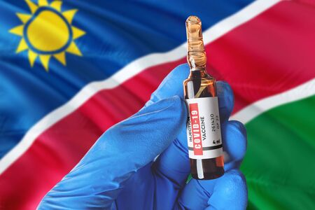 Namibia flag with Coronavirus Covid-19 concept. Doctor with blue protection medical gloves holds a vaccine bottle. coronavirus covid 19 vaccine research.