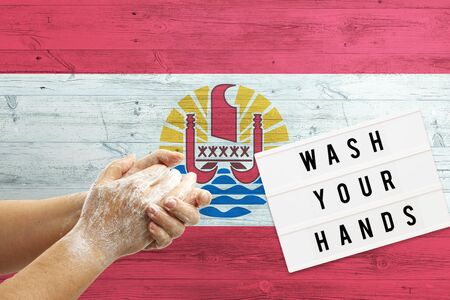 French Polynesia flag background on wooden surface. Minimal wash your hands board with minimal international hygiene concept hand detail.