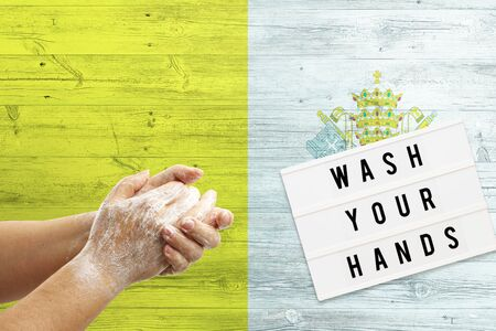Vatican City flag background on wooden surface. Minimal wash your hands board with minimal international hygiene concept hand detail. Reklamní fotografie