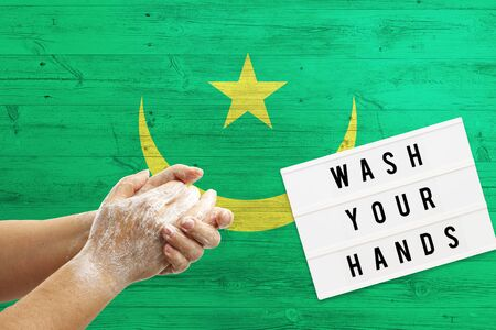 Mauritania flag background on wooden surface. Minimal wash your hands board with minimal international hygiene concept hand detail.