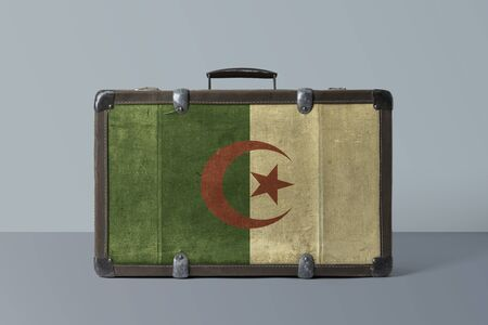 Algeria flag on old vintage leather suitcase with national concept. Retro brown luggage with copy space text.