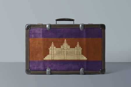 Cambodia flag on old vintage leather suitcase with national concept. Retro brown luggage with copy space text. 免版税图像