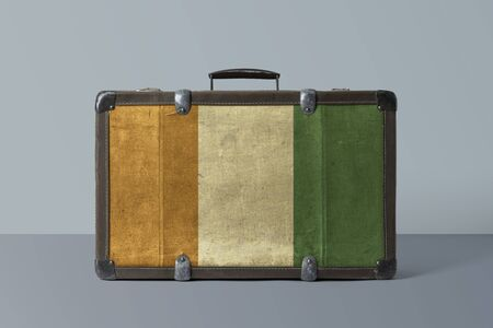 Cote D'Ivoire flag on old vintage leather suitcase with national concept. Retro brown luggage with copy space text.