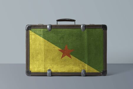 French Guiana flag on old vintage leather suitcase with national concept. Retro brown luggage with copy space text.