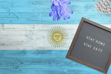 Argentina flag background on wooden table. Stay Home writing board, surgery gloves, pills with minimal national Covid 19 concept.