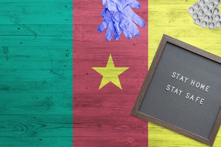 Cameroon flag background on wooden table. Stay Home writing board, surgery gloves, pills with minimal national Covid 19 concept.