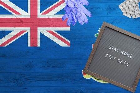 Cayman Islands flag background on wooden table. Stay Home writing board, surgery gloves, pills with minimal national Covid 19 concept.
