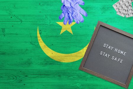 Mauritania flag background on wooden table. Stay Home writing board, surgery gloves, pills with minimal national Covid 19 concept.