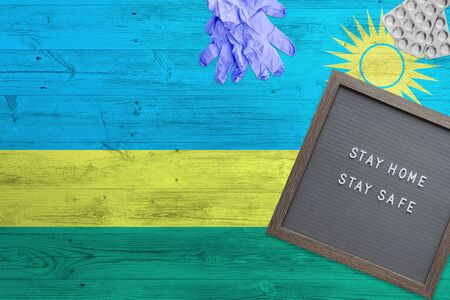 Rwanda flag background on wooden table. Stay Home writing board, surgery gloves, pills with minimal national Covid 19 concept.