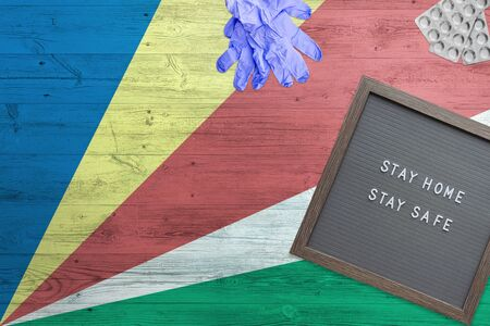Seychelles flag background on wooden table. Stay Home writing board, surgery gloves, pills with minimal national Covid 19 concept.