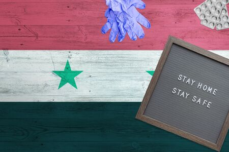 Syria flag background on wooden table. Stay Home writing board, surgery gloves, pills with minimal national Covid 19 concept.