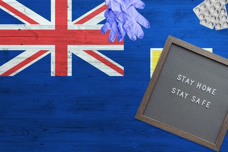 Turks And Caicos Islands flag background on wooden table. Stay Home writing board, surgery gloves, pills with minimal national Covid 19 concept.