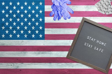 United States flag background on wooden table. Stay Home writing board, surgery gloves, pills with minimal national Covid 19 concept.