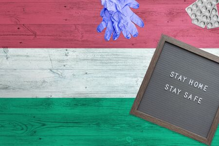 Hungary flag background on wooden table. Stay Home writing board, surgery gloves, pills with minimal national Covid 19 concept.