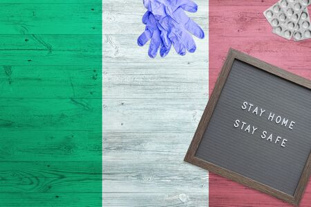 Italy flag background on wooden table. Stay Home writing board, surgery gloves, pills with minimal national Covid 19 concept.