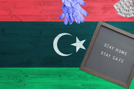 Libya flag background on wooden table. Stay Home writing board, surgery gloves, pills with minimal national Covid 19 concept.