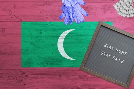 Maldives flag background on wooden table. Stay Home writing board, surgery gloves, pills with minimal national Covid 19 concept.