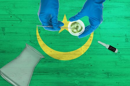 Mauritania flag on laboratory table. Medical healthcare technologist holding COVID-19 swab collection kit, wearing blue protective gloves, epidemic concept.
