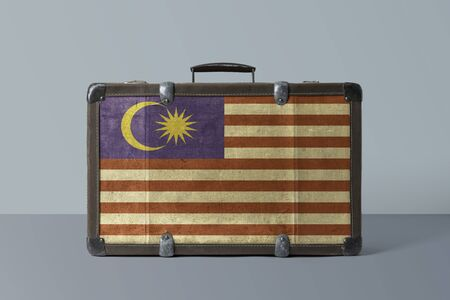 Malaysia flag on old vintage leather suitcase with national concept. Retro brown luggage with copy space text.
