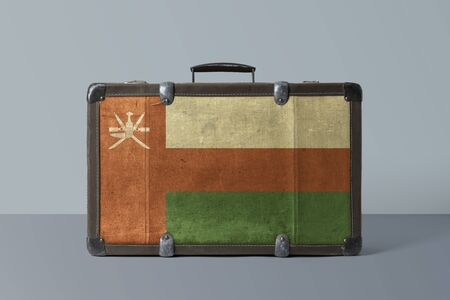 Oman flag on old vintage leather suitcase with national concept. Retro brown luggage with copy space text.