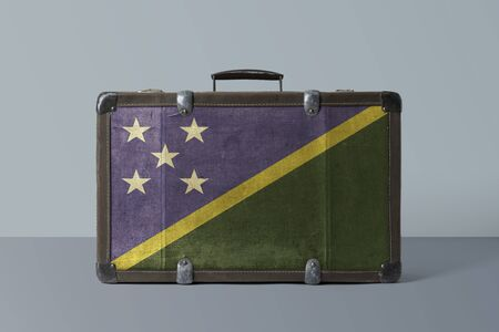 Solomon Islands flag on old vintage leather suitcase with national concept. Retro brown luggage with copy space text. Stok Fotoğraf