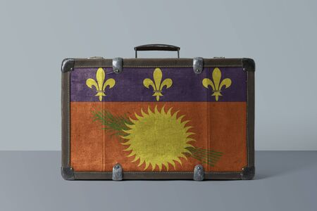 Guadeloupe flag on old vintage leather suitcase with national concept. Retro brown luggage with copy space text. 免版税图像