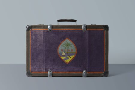Guam flag on old vintage leather suitcase with national concept. Retro brown luggage with copy space text.
