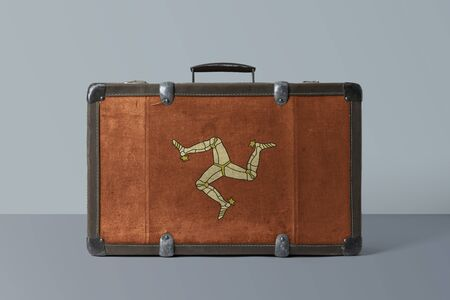 Isle Of Man flag on old vintage leather suitcase with national concept. Retro brown luggage with copy space text.