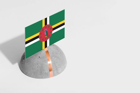 Dominica flag tagged on rounded stone. White isolated background. Side view minimal national concept.