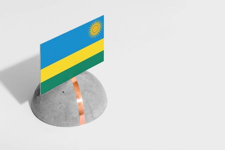 Rwanda flag tagged on rounded stone. White isolated background. Side view minimal national concept. Archivio Fotografico