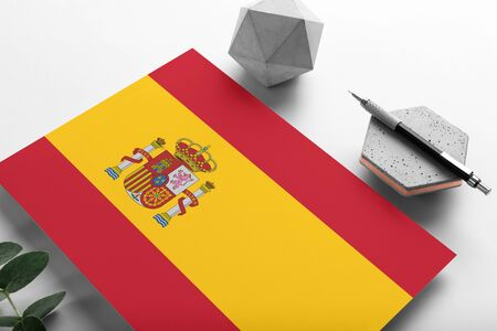 Spain flag on minimalist paper background. National invitation letter with stylish pen on stone. Communication concept.