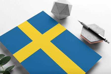 Sweden flag on minimalist paper background. National invitation letter with stylish pen on stone. Communication concept.