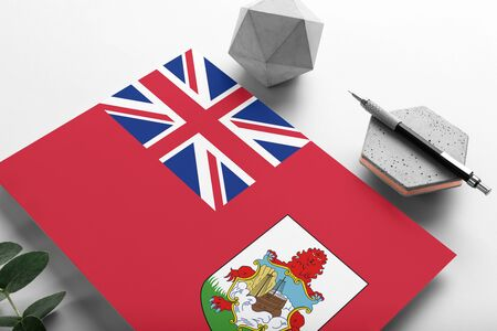 Bermuda flag on minimalist paper background. National invitation letter with stylish pen on stone. Communication concept.