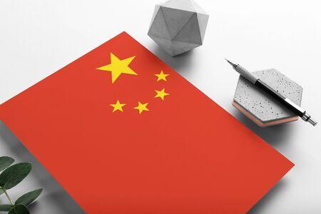 China flag on minimalist paper background. National invitation letter with stylish pen on stone. Communication concept.