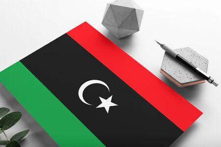 Libya flag on minimalist paper background. National invitation letter with stylish pen on stone. Communication concept.