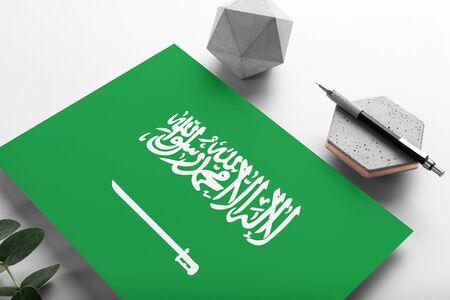 Saudi Arabia flag on minimalist paper background. National invitation letter with stylish pen on stone. Communication concept.