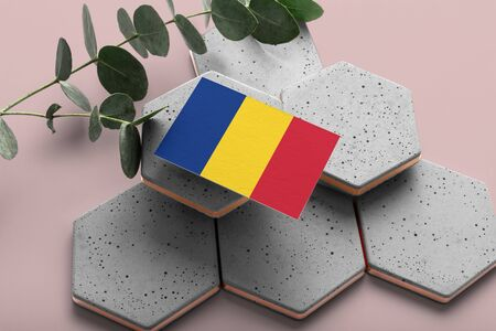 Romania flag on hexagon stylish stones. Pink copy space background. Flat lay, top view minimal national concept.