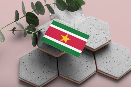 Suriname flag on hexagon stylish stones. Pink copy space background. Flat lay, top view minimal national concept.