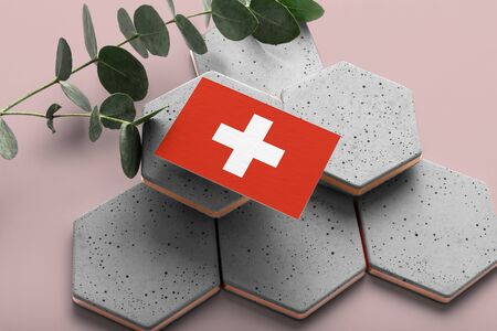 Switzerland flag on hexagon stylish stones. Pink copy space background. Flat lay, top view minimal national concept.