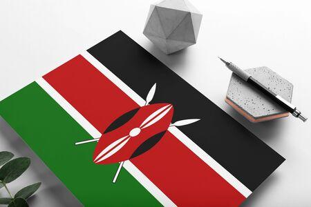 Kenya flag on minimalist paper background. National invitation letter with stylish pen on stone. Communication concept.
