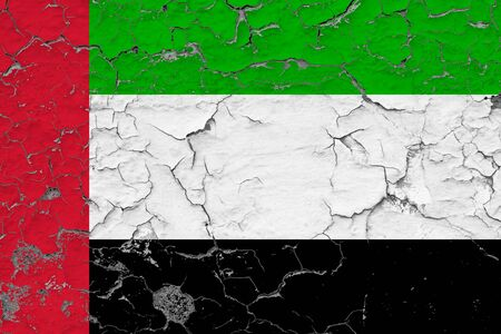 United Arab Emirates flag close up grungy, damaged and weathered on wall peeling off paint to see inside surface. Vintage concept.