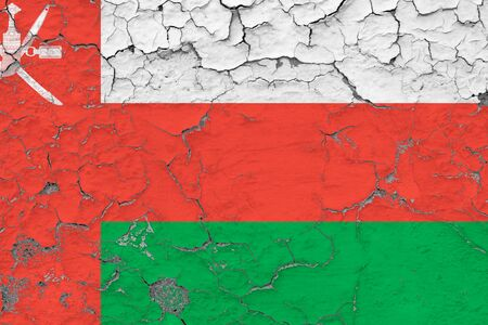 Oman flag close up grungy, damaged and weathered on wall peeling off paint to see inside surface. Vintage concept.
