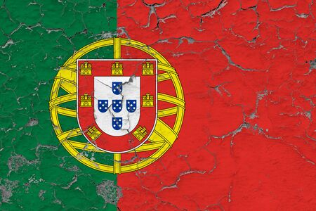 Portugal flag close up grungy, damaged and weathered on wall peeling off paint to see inside surface. Vintage concept.