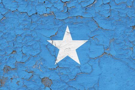 Somalia flag close up grungy, damaged and weathered on wall peeling off paint to see inside surface. Vintage concept.