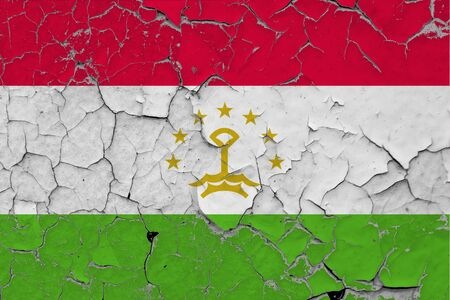 Tajikistan flag close up grungy, damaged and scratched on wall peeling off paint to see inside surface. Vintage National Concept.