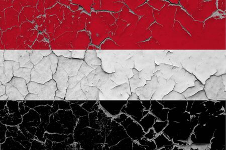Yemen flag close up grungy, damaged and scratched on wall peeling off paint to see inside surface. Vintage National Concept. Stockfoto