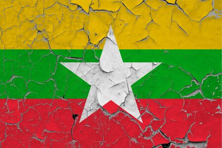 Myanmar flag close up grungy, damaged and scratched on wall peeling off paint to see inside surface. Vintage National Concept.
