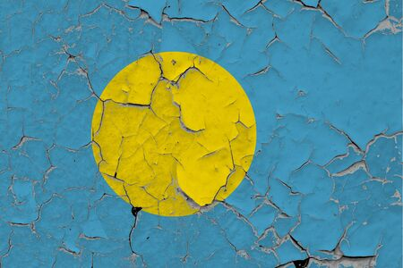 Palau flag close up grungy, damaged and scratched on wall peeling off paint to see inside surface. Vintage National Concept. Stockfoto
