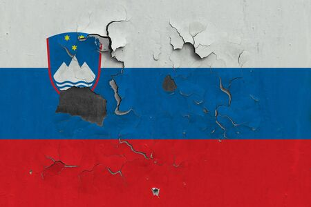 Slovenia flag close up old, damaged and dirty on wall peeling off paint to see inside surface. Vintage National Concept.